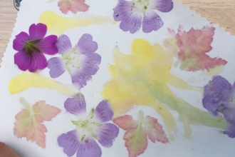 A printing with pink and yellow flowers and red and green leaves