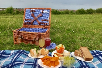 A picnic lunch laid out on a blanket on the grass