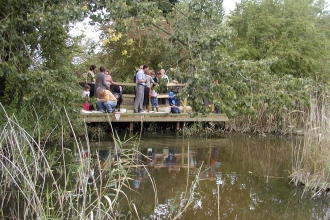 A group of people stand on a pond dipping platform