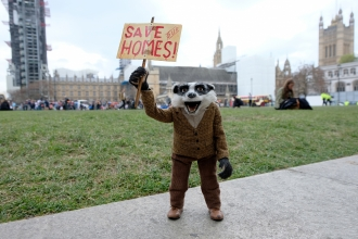Badger from the Wind in the Willows film holds up a 'Save Our Homes!' sign
