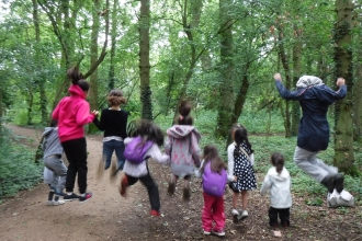 Families jumping in the woods by Rebecca Neal