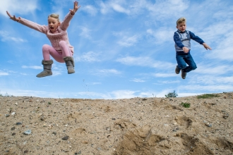 Children jumping in a blue sky