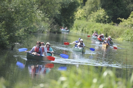 A group of people set off on canoes on the river Nene
