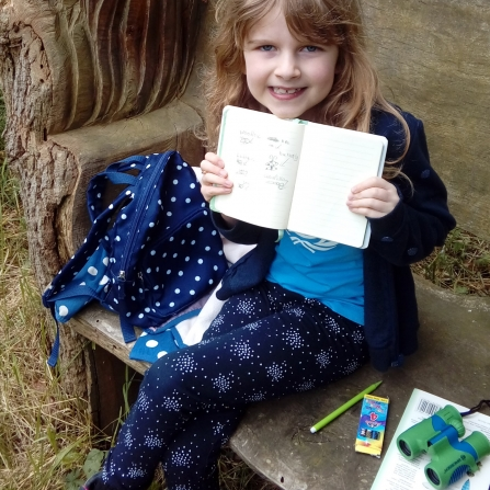 Emma shows off her sketches from a bench at Woodwalton Fen